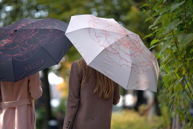 kaks naist jalutavad vihmavarjudega loven